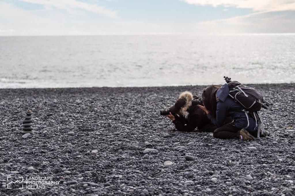 bending down to take photo of rocks on the black beach